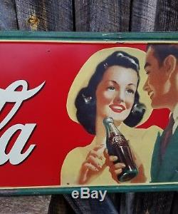 1942 Coca Cola Horizontal Sign with man and woman. 54inx18in. Painted metal